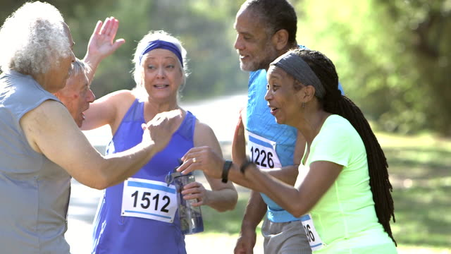 multi-ethnic group of seniors, high-fives after race - encouragement stock videos & royalty-free footage