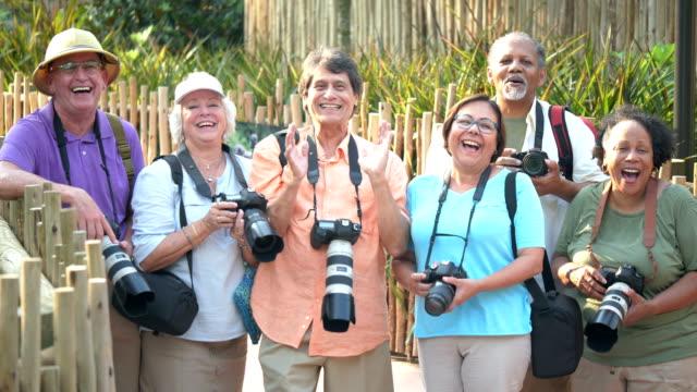 vidéos et rushes de groupe multiethnique d'aînés avec des caméras - tourisme