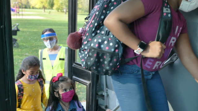 multi-ethnic group of students getting on the school bus - fatcamera stock videos & royalty-free footage