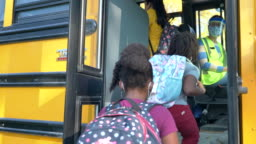 Multi-ethnic group of students getting on the school bus