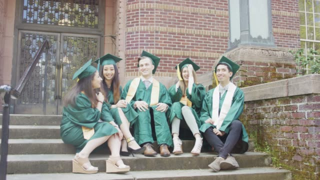 a multi-ethnic group of students sit and laugh together at their graduation. - graduation gown stock videos and b-roll footage