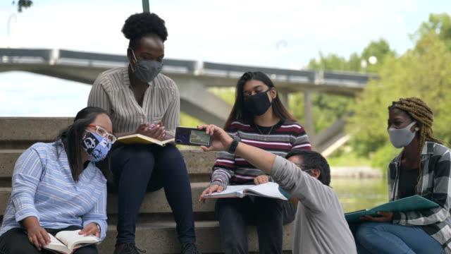 vidéos et rushes de groupe multiethnique d'étudiants s'asseyant sur le campus portant des masques - étudiant