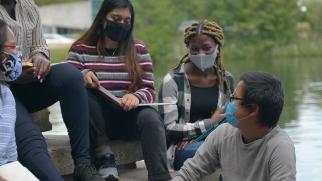 multi-ethnic group of students sitting on campus wearing masks - back to school stock videos & royalty-free footage