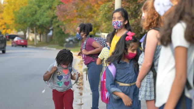 バスをつかむために道路を横断するのを待っている学生の多民族グループ - 初登校日点の映像素材/bロール