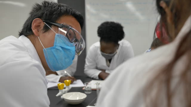 multi-ethnic group of students working in lab wearing face masks - stem topic stock videos & royalty-free footage