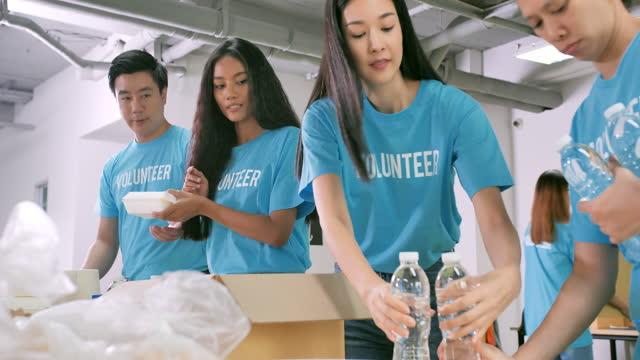gruppo multietnico di volontari che prepara la consegna gratuita di cibo per le persone da coronavirus di crisi covid-19. volontariato - beneficenza video stock e b–roll