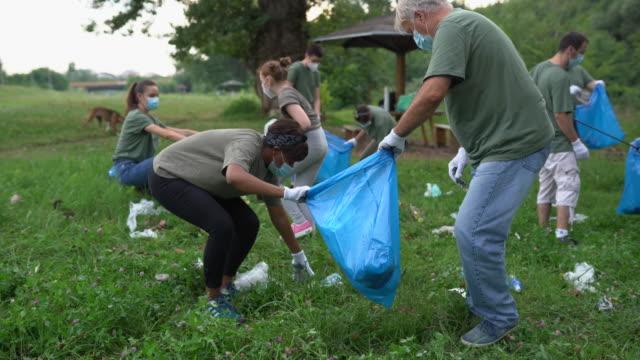 multi-ethnic group of volunteers cleaning public park during coronavirus pandemic - volunteer stock videos & royalty-free footage