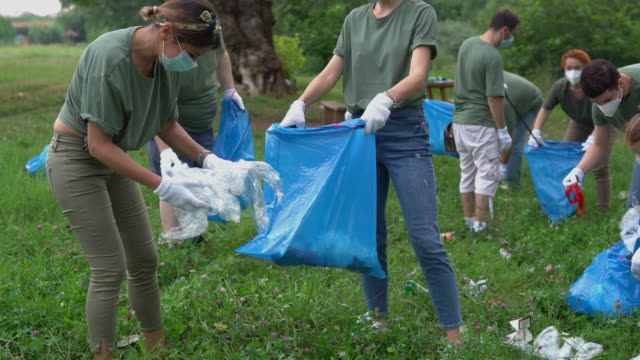 multi-ethnic group of volunteers cleaning public park during coronavirus pandemic - altruism stock videos & royalty-free footage