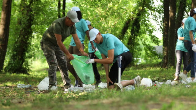 Multi-ethnic group of volunteers making an effort to clean a park