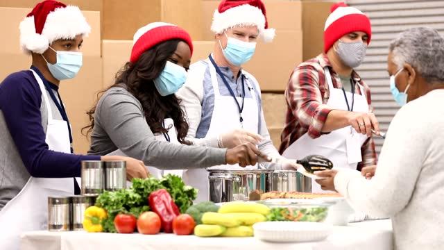 vídeos y material grabado en eventos de stock de grupo multiétnico de voluntarios trabajan en el comedor de sopas en navidad. - sin techo