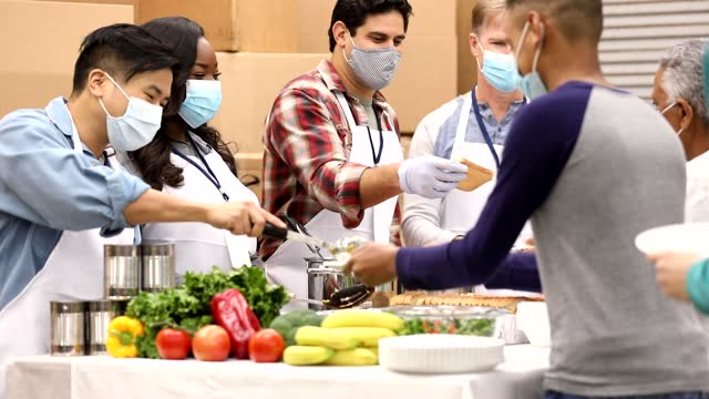 multi-ethnic group of volunteers work at soup kitchen. - soup kitchen stock videos & royalty-free footage