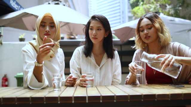 multi-ethnic group of women drinking water in the cafe - drinking glass stock videos & royalty-free footage