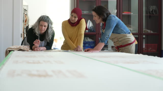 multi-ethnic group of women in a textile studio discussing design plans - art stock videos & royalty-free footage