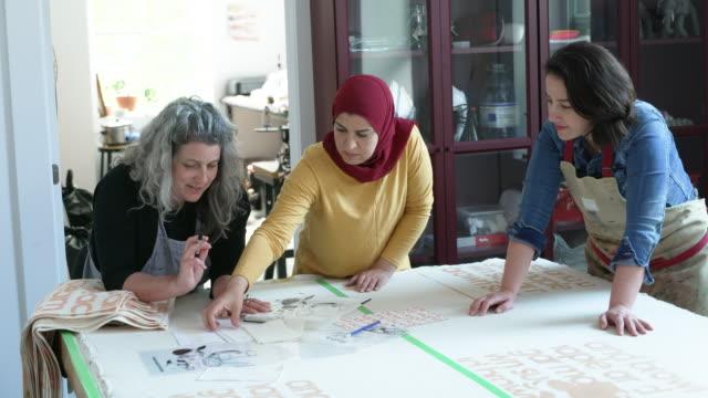 stockvideo's en b-roll-footage met multi-etnische groep vrouwen in een textielstudio die ontwerpplannen bespreekt - drukker