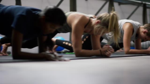 a multi-ethnic group of women in their twenties hover in the plank position and then stretch on the floor of a barre exercise studio - barre stock videos & royalty-free footage