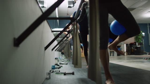 eine multi-ethnische gruppe von frauen in den zwanzigern durchführen beinübungen an einer ballettstange in einer übung studio - auf einem bein stock-videos und b-roll-filmmaterial