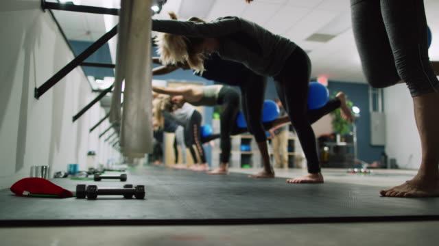 un gruppo multietnico di donne ventenni esegue esercizi per le gambe in un ballet barre in uno studio di esercizi - pilates video stock e b–roll