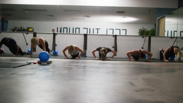 a multi-ethnic group of women in their twenties practice push-ups on the floor of an exercise studio - barre fitness stock videos and b-roll footage