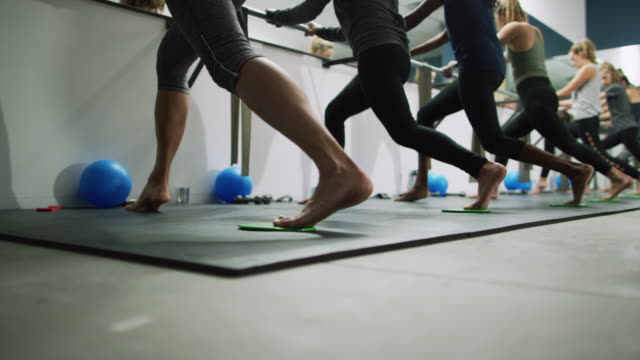 a multi-ethnic group of women in their twenties pulse in a lunge position at a ballet barre in an exercise studio - barre stock videos & royalty-free footage