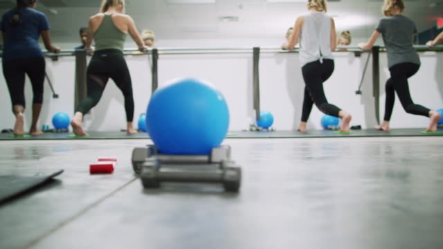 a multi-ethnic group of women in their twenties pulse in the lunge position at a ballet barre in the background at an exercise studio with a fitness ball and hand weights in the foreground - barre fitness stock videos and b-roll footage