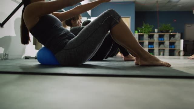 a multi-ethnic group of women in their twenties pulse while leaning back on fitness balls with their hands outstretched at an exercise studio - pilates stock videos & royalty-free footage