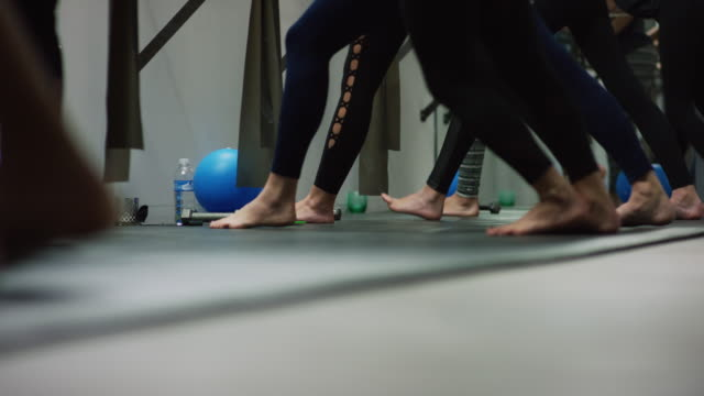 a multi-ethnic group of women in their twenties stretch their legs at a ballet barre in an exercise studio - barre stock videos & royalty-free footage