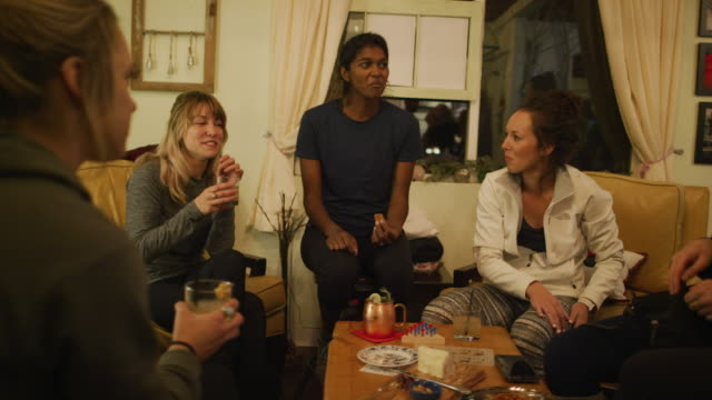 a multi-ethnic group of women in their twenties talk and eat in a cozy indoor setting - ladies' night stock videos and b-roll footage
