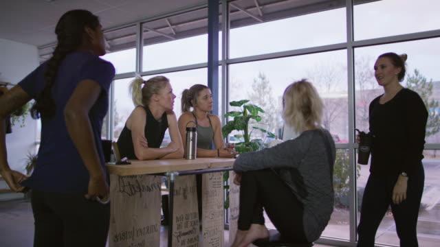 vidéos et rushes de un groupe multiethnique de la femme dans la vingtaine discute dans un groupe en vêtements d'exercice dans une pièce bien éclairée avec windows - multi ethnic group