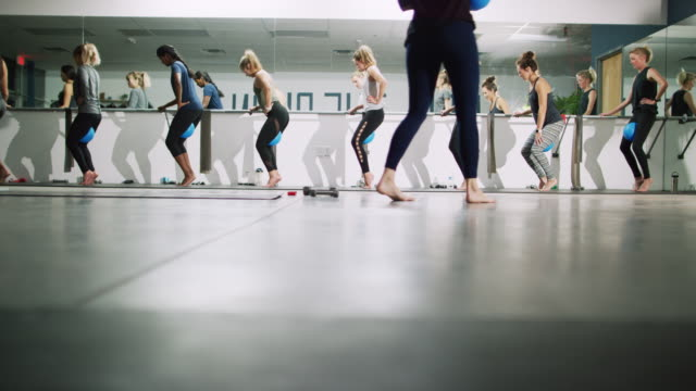 a multi-ethnic group of women of mixed ages stand on tiptoe with fitness balls between their thighs stand at a ballet barre in an exercise studio while a fitness instructor watches - tiptoe stock videos & royalty-free footage