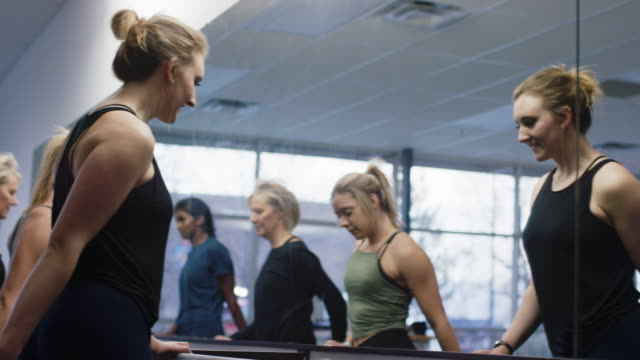 a multi-ethnic group of women of mixed ages step up and stretch at a ballet barre in front of a large mirror in an exercise studio - mirror stock videos & royalty-free footage