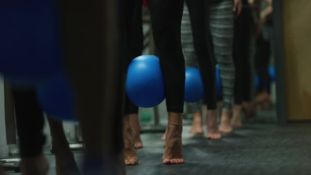 a multi-ethnic group of women pulse with a fitness ball between their calves in a class at an exercise studio - barre stock videos & royalty-free footage