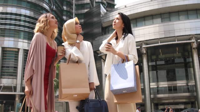 Multietnisk grupp kvinnor står framför Petronas towers