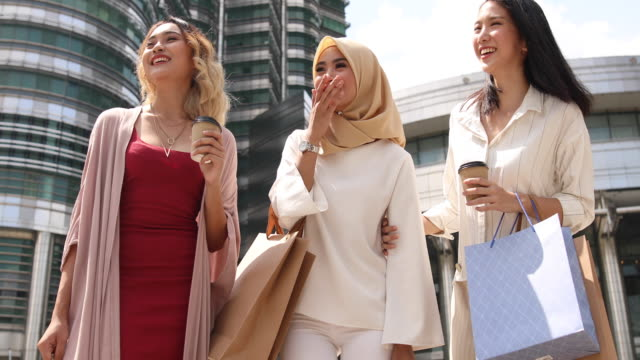 Multi-ethnic group of women standing in front of the Petronas towers