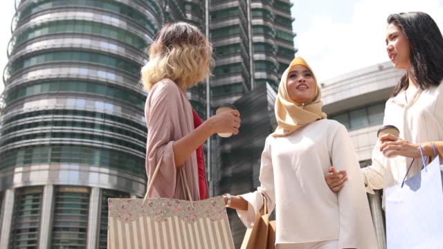 Multietnisk grupp kvinnor står framför Petronas towers efter shopping