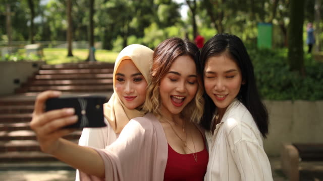 multi-ethnic group of women taking a selfie in the park - three people stock videos & royalty-free footage