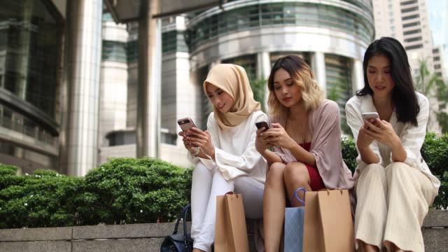 vídeos de stock, filmes e b-roll de grupo multiétnico de mulheres usando telefones inteligentes em frente as torres petronas - vestuário modesto