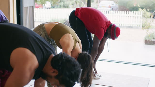 Multi-ethnic group of yoga students in standing forward bend