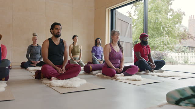 multi-ethnic group raising arms in yoga studio - cross legged stock videos & royalty-free footage