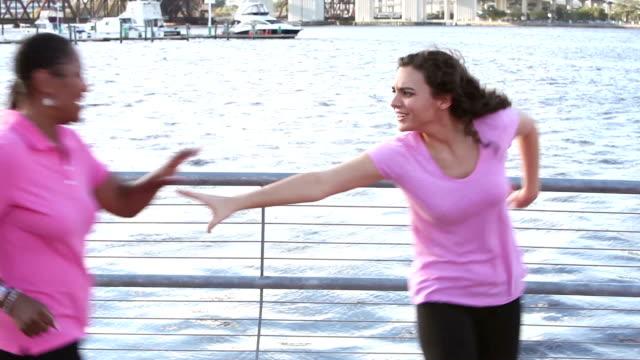 Multi-ethnic group, women in pink walking on waterfront