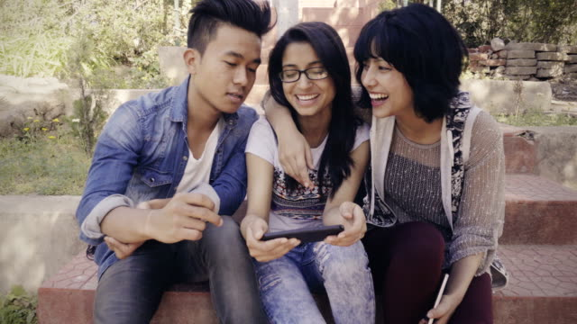 multiethnic happy, college friends together sharing smart phone. - university student stock videos and b-roll footage