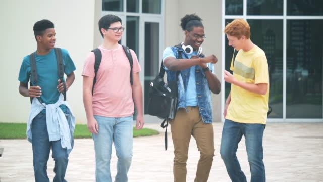 vidéos et rushes de des lycéens multiethniques marchant et parlant - élève du secondaire