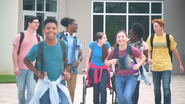 stockvideo's en b-roll-footage met multi-etnische middelbare schoolstudenten die lopen en spreken - 14 15 years