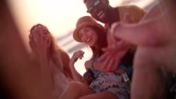 Multi-ethnic hipster couple having fun with friends at beach party