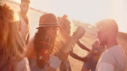 Multi-ethnic hipster friends dancing at summer beach party at sunset
