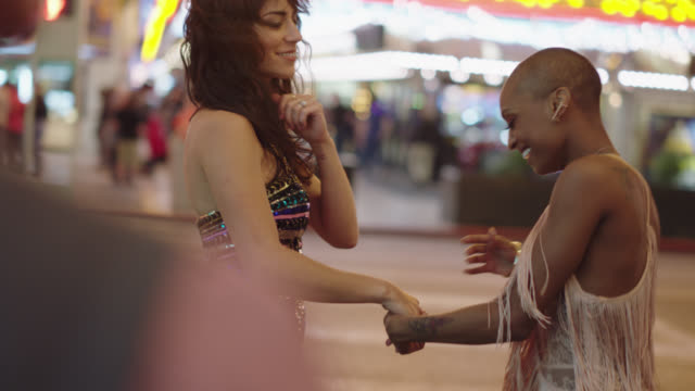 multi-ethnic lesbian newlyweds dance together on a street corner on fremont st. in las vegas - dancer stock videos & royalty-free footage