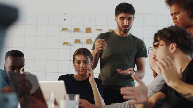 multi-ethnic male and female programmers discussing over laptop during meeting in coworking office - 20 29 years stock videos & royalty-free footage