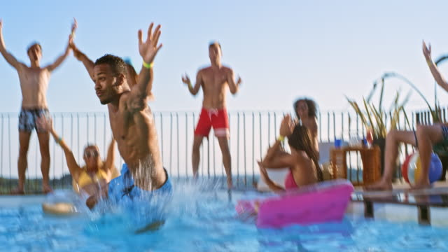SLO MO DS Multiethnic man doing a funny jump into the pool while friends are cheering for him