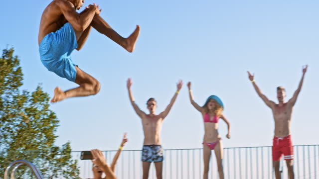 slo mo ds multiethnic man jumping into the pool and his friend are cheering for him - arms raised stock videos & royalty-free footage