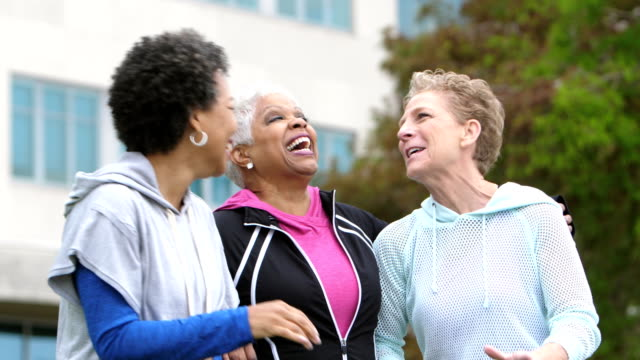 Multi-ethnic mature women outdoors talking, laughing