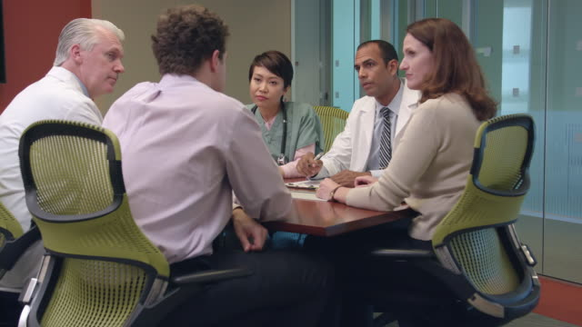 multi-ethnic medical professionals meet in office - ws - manager stock videos & royalty-free footage
